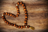 Heart shape of rosary on wooden background — Stock Photo