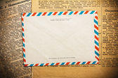 Envelope on aged newspaper — Stock Photo