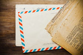 Old envelope with aged newspaper on wooden background — Stock Photo