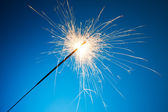 Sparkler on blue background — 图库照片