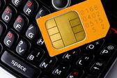 Sim card on smart phone keyboard — Stock Photo