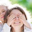 Beautiful little girl with hand on eyes of mother — Stock Photo