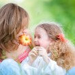 Young mother and her daughter eating — Stock Photo #11431175