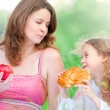 Young mother and her daughter eating — Stock Photo