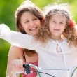 Young mother and her daughter on bicycle — Stock Photo