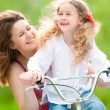 Young mother and her daughter on bicycle — Stock Photo #11431185