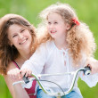 Young mother and her daughter on bicycle — Stock Photo #11431186
