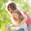 Foto Stock: Young mother and her daughter on bicycle