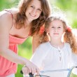 Young mother and her daughter on bicycle — Stockfoto