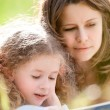 beautiful little girl reading book with ger mother — Stock Photo