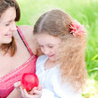Young mother and her daughter with apple — Stock Photo