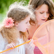 Little girl and her mother with butterfly net — Stock Photo #11431216