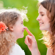Mother touching her daughter on her nose — Stock Photo