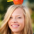 Young student girl with apple on her head — Stock Photo