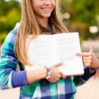 Young student girl showing something in book — Stock Photo