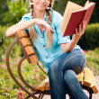 Beautiful young student girl reading book — Stock Photo