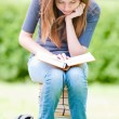 Happy student girl sitting on pile of books — ストック写真