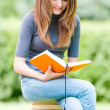 Happy student girl sitting on pile of books — Stock Photo