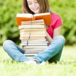 Happy student girl sitting on grass and reading — 图库照片