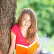 Happy student girl reading book — Stok fotoğraf