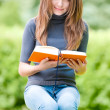 Happy student girl sitting on pile of books — Stock Photo #11436608