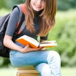 Happy student girl sitting on pile of books — Stock Photo #11436618