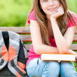 Stock Photo: Happy student girl sitting on bench with book