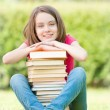 Happy student girl sitting near pile of books — Stock Photo #11436648