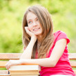Happy student girl sitting on bench with books and dreaming — Stok fotoğraf