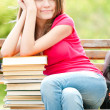Happy student girl sitting on bench with pile of books — Stock Photo #11436656