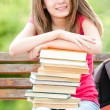 Happy student girl sitting on bench with books and smiling — Stock Photo #11436662