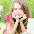 Happy student girl lying on grass with laptop computer - Stock Photo