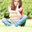 Sad student girl sitting near pile of books — Stock Photo