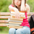 Sad young student girl sitting on bench with books — Stock Photo