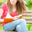 Serious student girl sitting on bench with book — ストック写真