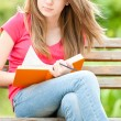 Serious student girl sitting on bench with book — Stock fotografie
