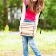 Young student girl holding big pile of heavy books — Stock Photo