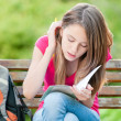 Young student girl sitting on bench — Stock Photo