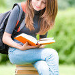 Young student girl sitting on pile of books — ストック写真