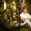 Young woman with bicycle in forest — Stok fotoğraf