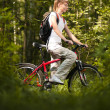 Young woman with bicycle in forest — Stock Photo #11438427