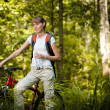 Young woman with bicycle in forest — Stock Photo #11438428