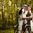 Young woman with bicycle in forest — Stock Photo #11438429