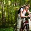 Stock Photo: Young woman with bicycle in forest
