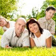 Family of four on grass — Stock Photo