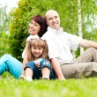 Family of three on grass - Stock Photo