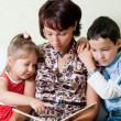 Stock Photo: A mother is reading a book to her kids