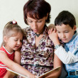 A mother is reading a book to her kids — Stock Photo
