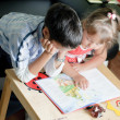 Boy and his sister are reading book — Stockfoto #11438836