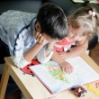 Foto Stock: Boy and his sister are reading book
